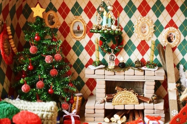 Interior de ano novo na casa de brinquedo. sala com lareira e árvore de natal para bonecas e brinquedos pequenos Foto Premium