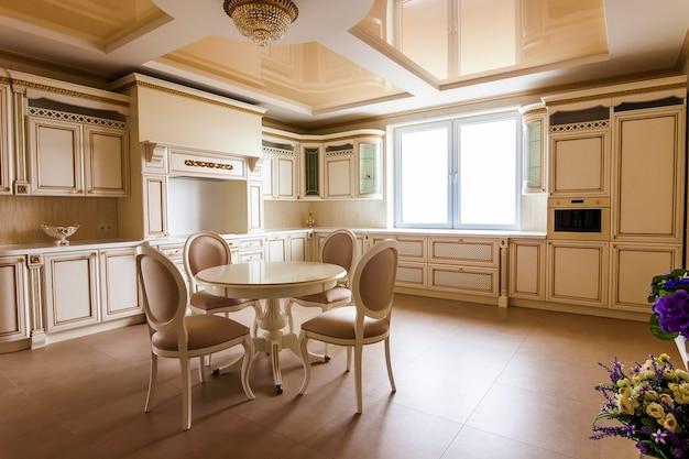 Interior de cozinha moderna e equipada de luxo. cozinha em casa de luxo com armários bege. mesa e cadeiras Foto Premium