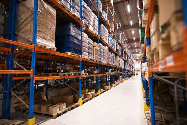 Interior de grande armazém de distribuição com prateleiras repletas de paletas e produtos prontos para o mercado Foto gratuita