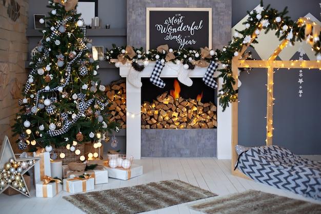 Interior de natal da sala de estar com árvore de natal decorada, lareira com meias de natal e cama de madeira em forma de casa. interior elegante do quarto das crianças, decoração do quarto em loft de estilo rústico Foto Premium