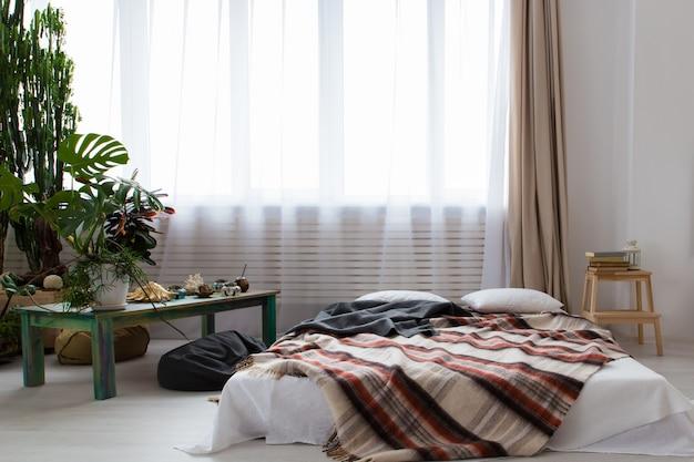 Interior de um moderno estúdio com muitas plantas e uma cama no chão Foto Premium