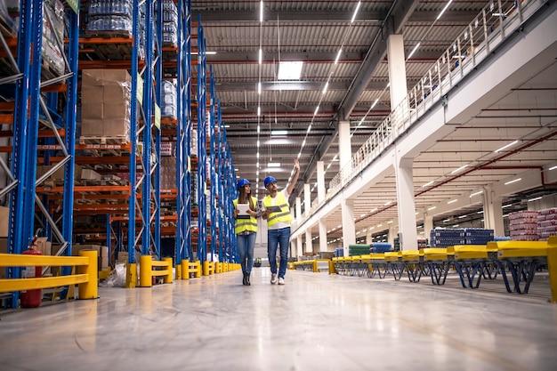 Interior do armazém de distribuição com trabalhadores vestindo capacetes e jaquetas reflexivas andando na área de armazenamento Foto gratuita
