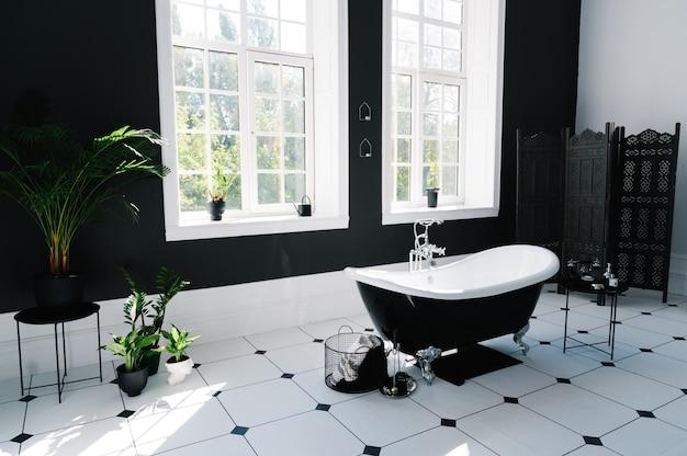 Interior do banheiro com janelas e banheira com pés Foto Premium