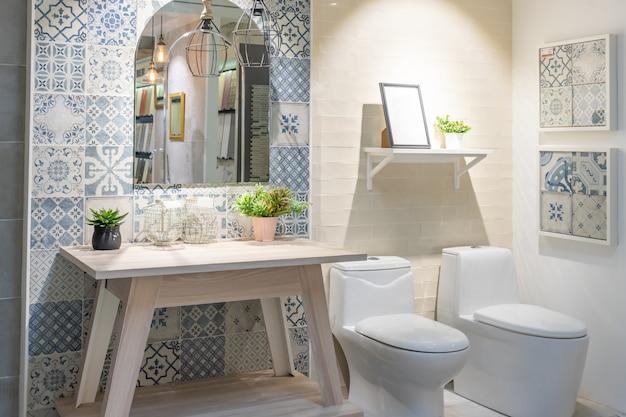 Interior do banheiro com parede branca, móveis vintage, toalhas, vaso sanitário e pia Foto Premium