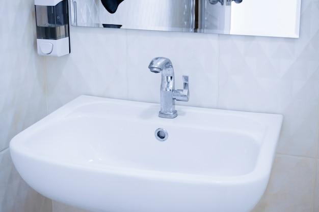 Interior do banheiro público limpo, pia branca interior do banheiro público com de lavar as mãos e espelho Foto Premium