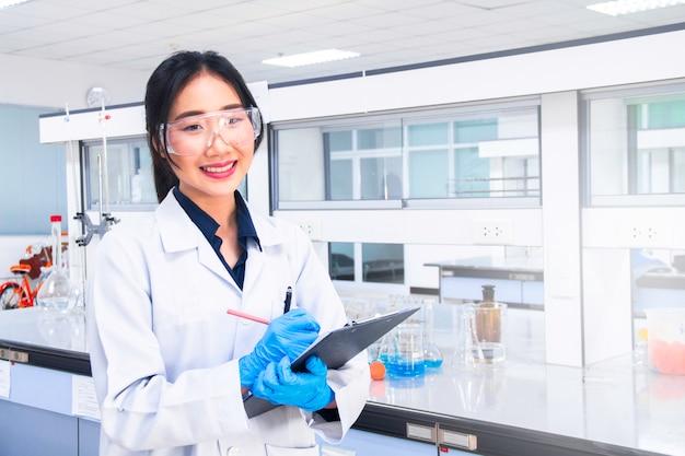Interior do laboratório médico ou de química moderno limpo. cientista de laboratório trabalhando em um laboratório. conceito de laboratório com químico de mulher asiática. Foto Premium