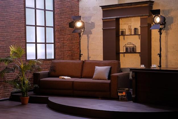 Interior escuro da sala com janela, sofá, planta e lâmpadas. Foto Premium