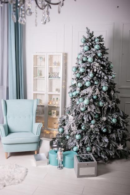 Interior luminoso com sofá, poltrona e árvore de natal Foto Premium