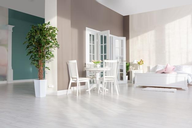 Interior luxuoso e caro de um apartamento de plano aberto em cores claras. quarto moderno e elegante com design minimalista, área para refeições e espaço para hóspedes. Foto Premium