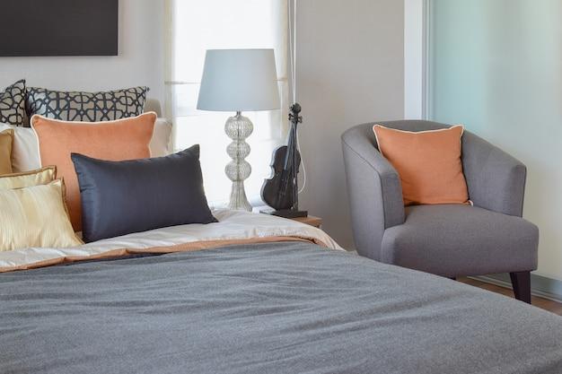 Interior moderno quarto com almofada laranja na cadeira cinza e candeeiro de mesa de cabeceira em casa Foto Premium