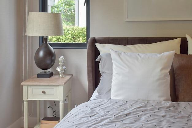 Interior moderno quarto com travesseiro branco e marrom na cama e abajur decorativo Foto Premium