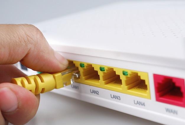 Internet modem roteador hub com a mão segurando o cabo amarelo conectando isolado fundo branco Foto Premium