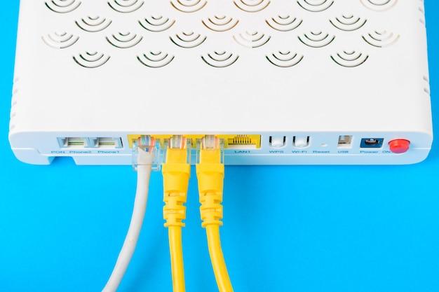 Internet modem roteador hub com um cabo de ligação em fundo azul Foto Premium