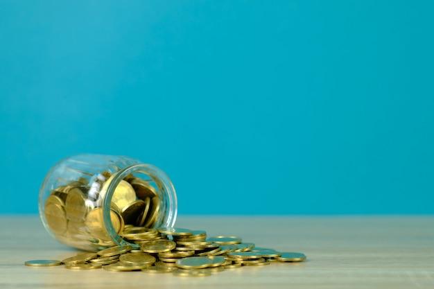 Inventa pilhas e dinheiro da moeda de ouro no frasco de vidro na tabela com fundo verde, para salvar para o conceito futuro da finança da operação bancária. Foto Premium