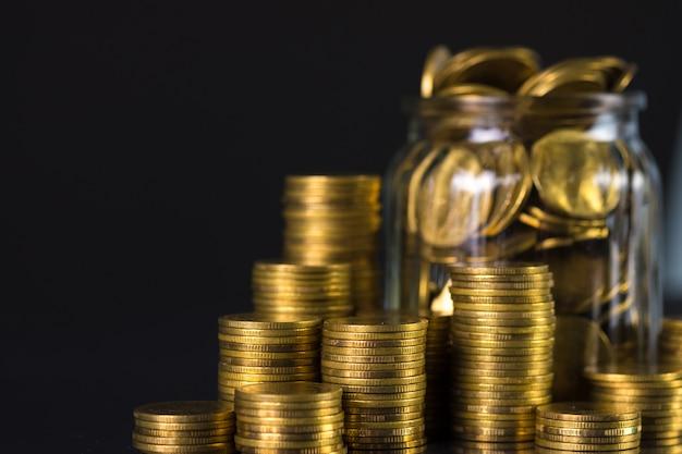 Inventa pilhas e dinheiro da moeda de ouro no frasco de vidro no fundo escuro, para salvar para o conceito futuro da finança da operação bancária. Foto Premium