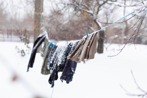 Inverno. as roupas estão secando na rua. roupas cobertas de neve secam com uma corda apertada. Foto Premium