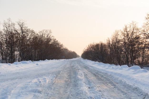 Inverno estrada mal limpa. estrada no campo repleta de neve. paisagem do inverno com montes de neve Foto Premium