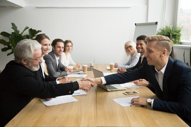 Investidor sênior, comprando, startup, handshaking, jovem, empreendedor, em, reunião grupo Foto gratuita