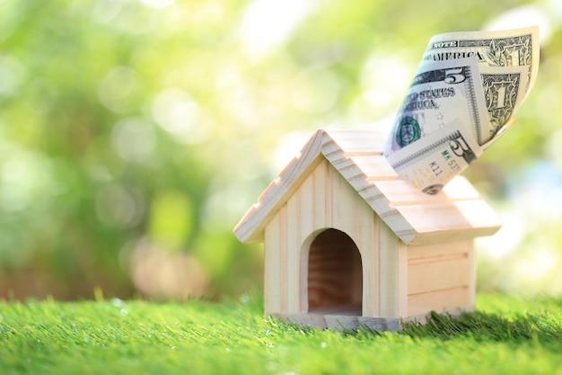 Investimento empresarial e imobiliário, casa modelo com notas, poupar para preparar no futuro Foto Premium