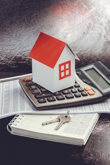 Investimento imobiliário. casa, chave e calculadora na mesa Foto Premium
