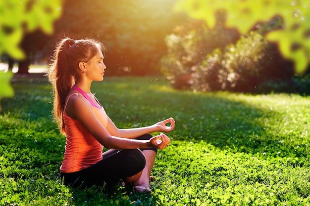 Ioga. jovem mulher praticando ioga ou dançar ou esticar na natureza no parque. conceito de estilo de vida de saúde Foto Premium