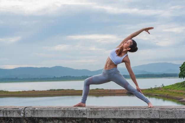 Ioga praticando da mulher bonita pelo lago com montanha. Foto Premium