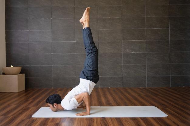 Iogue experiente fazendo pose de ioga de cabeça pra baixo no ginásio Foto gratuita