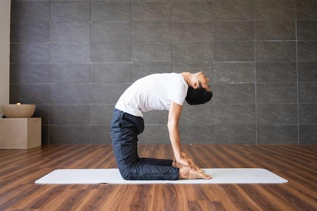 Iogue fazendo pose de ioga de camelo no ginásio Foto gratuita