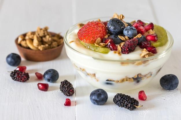 Iogurte com morango, mirtilos, kiwi, granola, romã em uma tigela de vidro e mel em madeira branca Foto Premium
