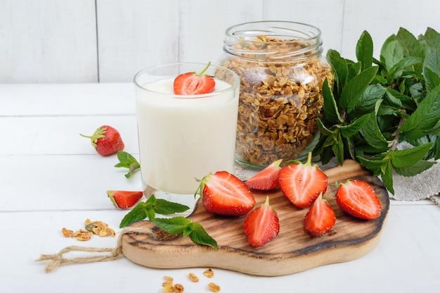 Iogurte com morangos e granola em cima da mesa Foto Premium