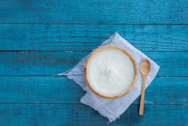 Iogurte grego ou creme de leite em uma bacia de madeira na opinião de tampo da mesa azul. nutrição de alimentos saudáveis. Foto Premium