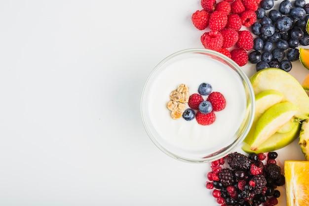 Iogurte perto de frutas e bagas Foto gratuita