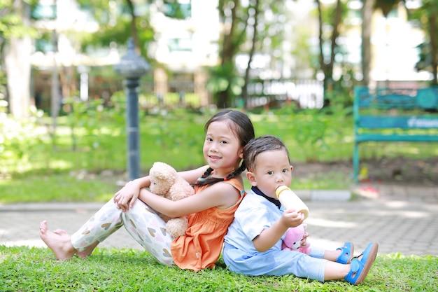 Irmã asiática e irmão mais novo no jardim. criança menina afago ursinho boneca e menino chupar leite da garrafa. Foto Premium
