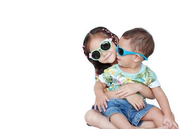 Irmã asiática pequena do retrato que abraça o irmão mais novo que veste um vestido e óculos de sol do verão das flores isolados. conceito de moda e verão. Foto Premium