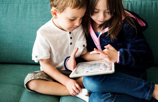 Irmãos jogando em tablet