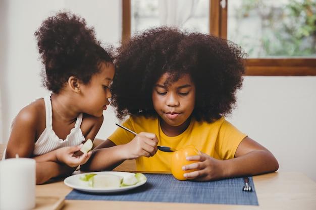 Irmã mais nova bonitinha olhando interessante sua irmã mais velha tentar aprender a comer vegetais. Foto Premium
