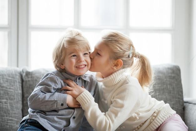Irmã mais velha da criança que abraça o irmão pequeno mais novo de beijo em casa Foto gratuita