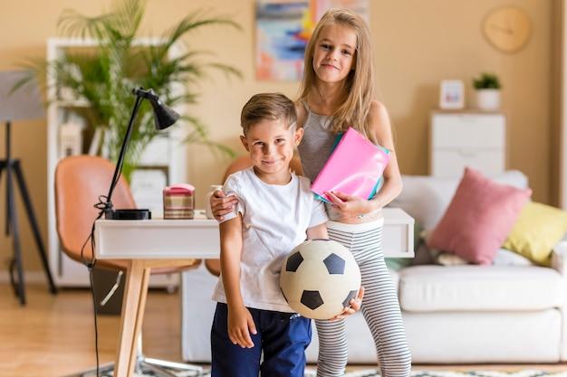 Irmã mais velha e irmão segurando cadernos e bola de futebol Foto gratuita