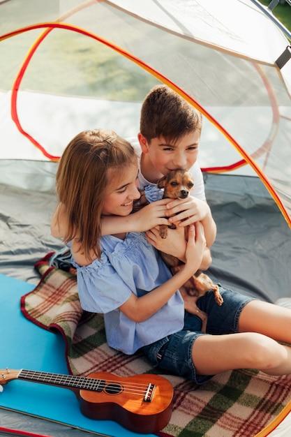 Irmão e irmã amando seu animal de estimação sentado na tenda Foto gratuita