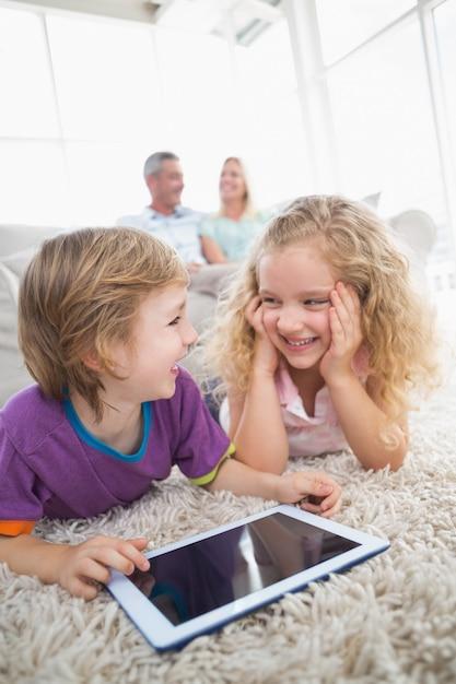 Irmão e irmã com tablet digital no tapete Foto Premium