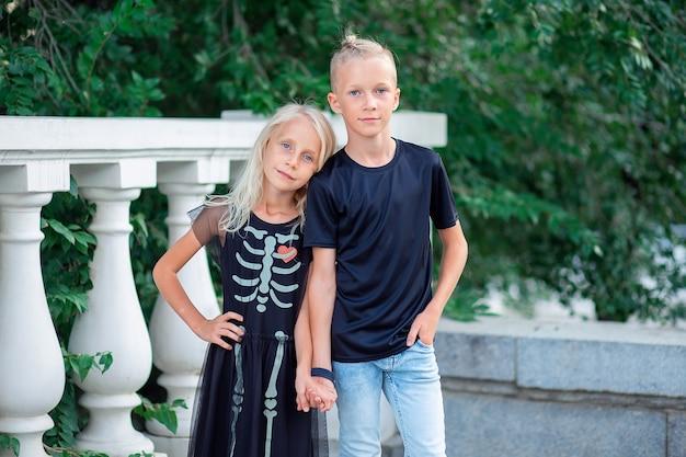 Irmão e irmã em roupas pretas da moda segurando a alça Foto Premium