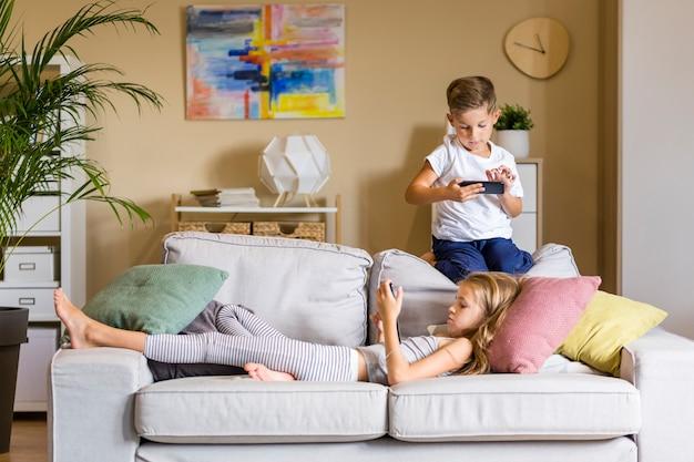 Irmão e irmã na sala olhando para seus telefones Foto gratuita