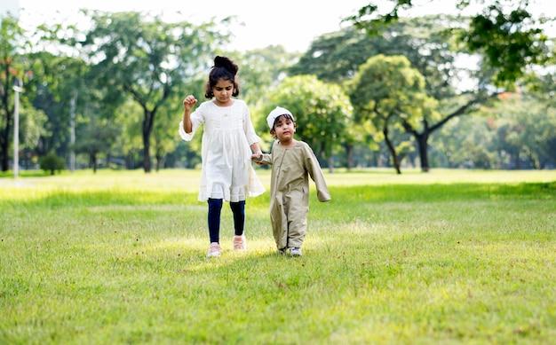 Irmão muçulmano e irmã brincando no parque Foto Premium