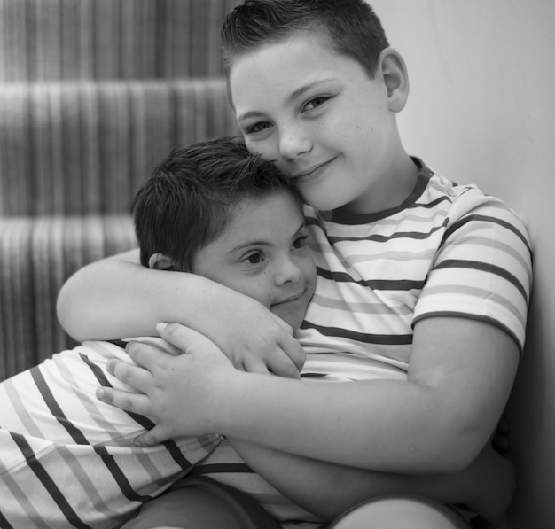 Irmãos abraçando nas escadas Foto Premium