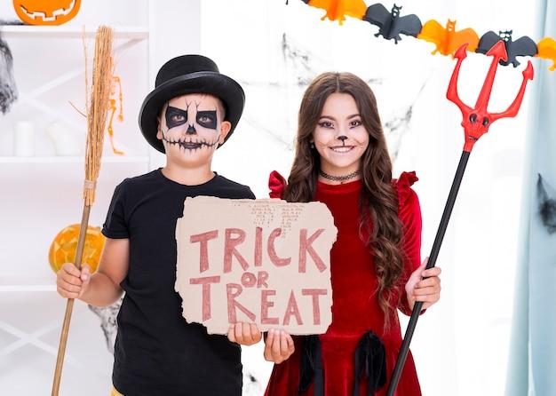 Irmãos bonitos segurando doces ou travessuras sinal para o halloween Foto gratuita