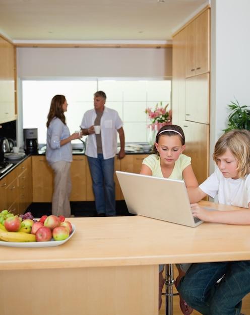 Irmãos com caderno na cozinha e pais atrás deles Foto Premium