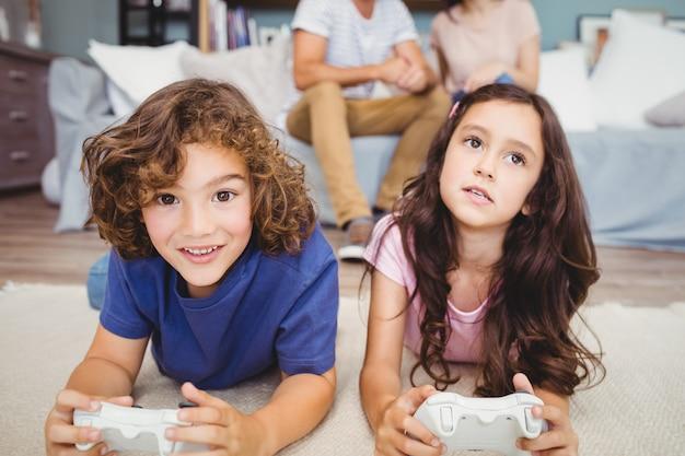 Irmãos com jogar videogame no tapete Foto Premium