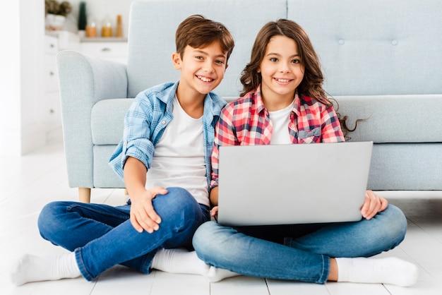 Irmãos de vista frontal no chão usando laptop Foto gratuita
