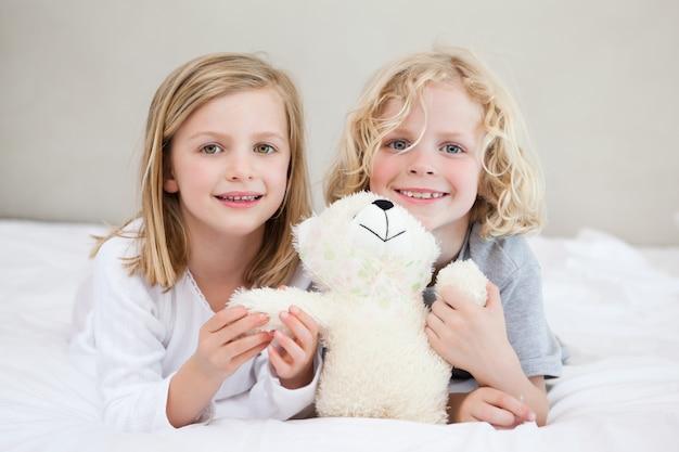 Irmãos deitado na cama com ursinho Foto Premium