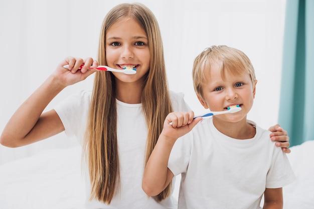 Irmãos escovando os dentes juntos Foto gratuita